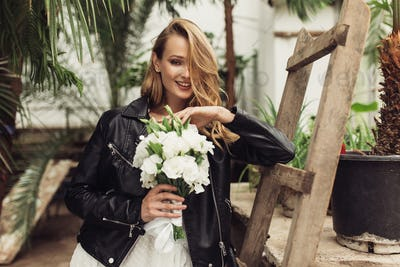 Young cheerful woman in black leather jacket and white dress wit
