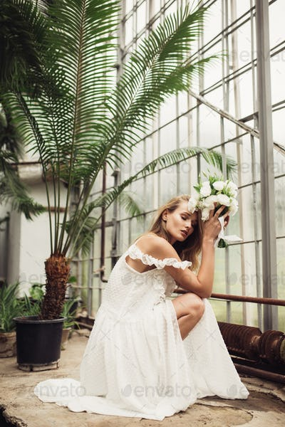 Young beautiful bride in white dress sitting down holding little