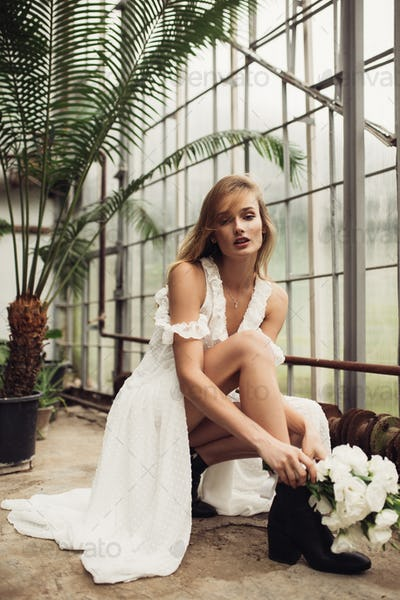 Young pretty bride in white dress sitting down holding little bo