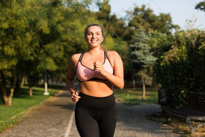 Young cheerful plus size woman in pink sporty top and leggings j