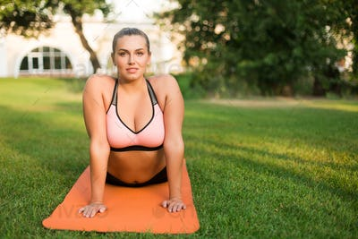 Young attractive plus size woman in sporty top and leggings prac