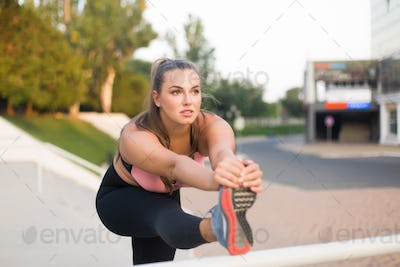 Young pensive plus size woman in sport top and leggings stretchi