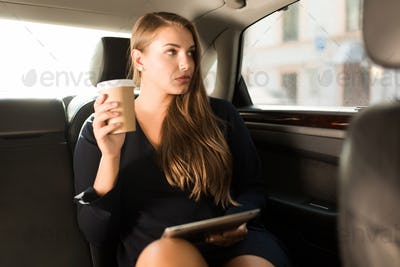 Young pensive businesswoman in black dress sitting on back seat