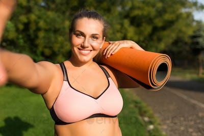 Young joyful plus size woman in pink sporty top holding orange y