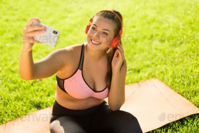 Young cheerful plus size woman in pink sporty top and leggings w