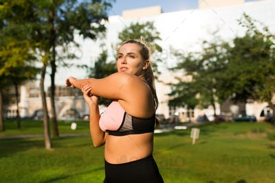Beautiful pensive plus size girl in pink sporty top and leggings