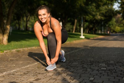 Young beautiful smiling plus size woman in sporty top and leggin