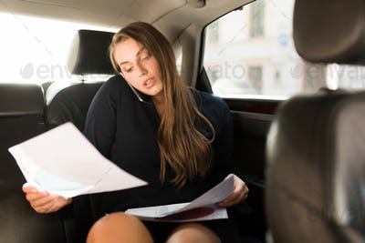 Young busy businesswoman in black dress sitting on back seat in