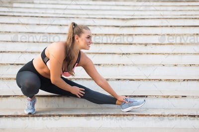 Joyful plus size girl in sporty top and leggings happily stretch