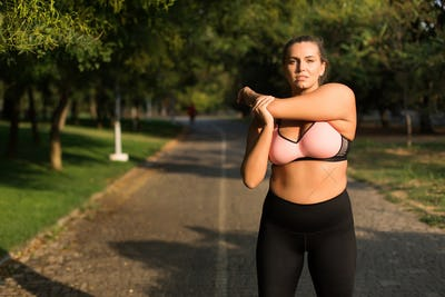 Beautiful plus size girl in pink sporty top and leggings dreamil