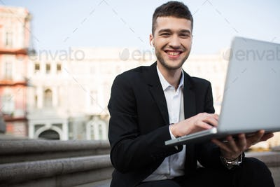 Young joyful businessman in classic black jacket and shirt with