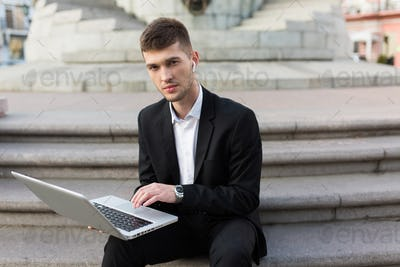 Young handsome businessman in classic black suit with wireless e