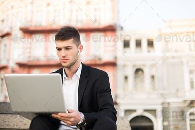 Young serious businessman in black suit and white shirt with wir