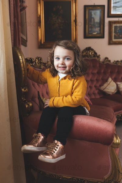 Girl toddler in a living room with baroque decor.