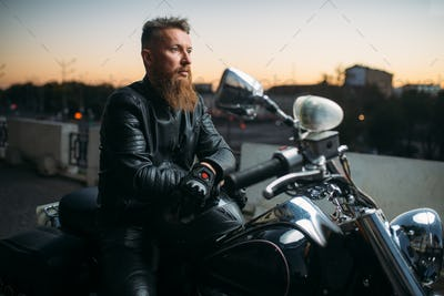 Biker poses on a motorcycle in city on sunset