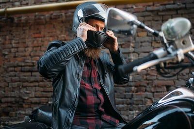 Biker puts on helmet before riding on chopper
