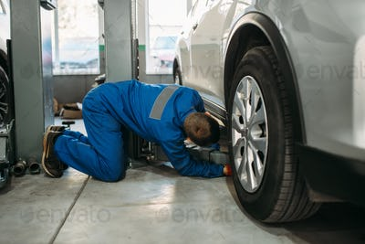 Repairman adjusts lift jack in car service