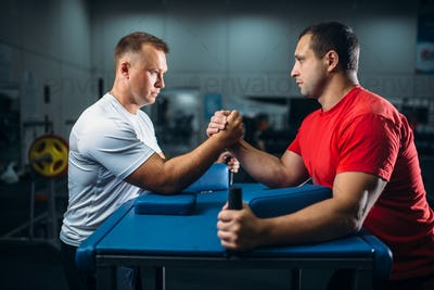 Two arm wrestlers on starting position, wrestling