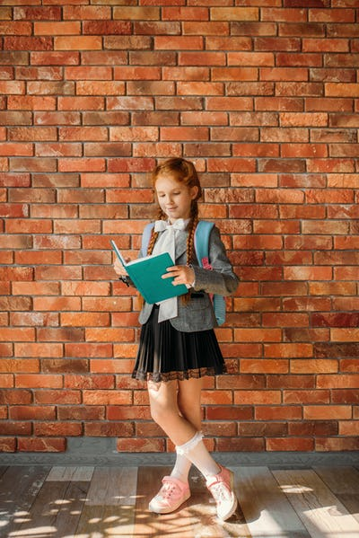 Cute schoolgirl with schoolbag reading a textbook