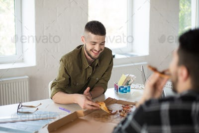 Young smiling man with beard in shirt happily eating pizza while