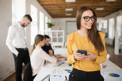 Young business woman in eyeglasses joyfully looking aside while
