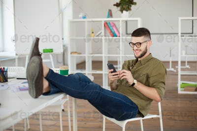 Young smiling man in eyeglasses and shirt happily using cellphon