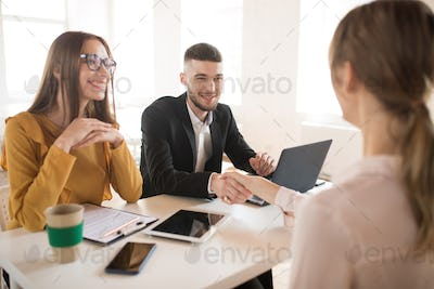 Cheerful business man with laptop and business woman in eyeglass