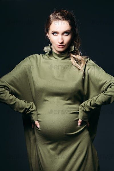 Front view of beautiful and fashionable pregnant brunette woman at dark studio. Pretty and stylish