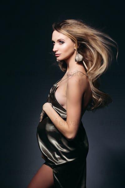 Blondie pegnant female posing at dark studio in gray silk dress