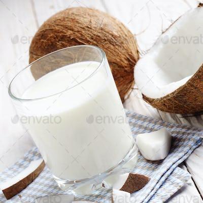 Drinking glass of milk or yogurt on blue napkin on white wooden