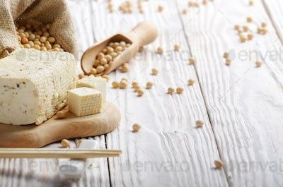 Soy Bean curd tofu on cutting board and in hemp sack on white wo