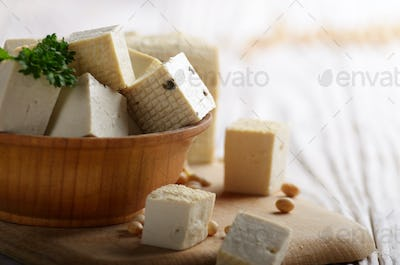 Soy Bean curd tofu in wooden bowl on white wooden kitchen table.