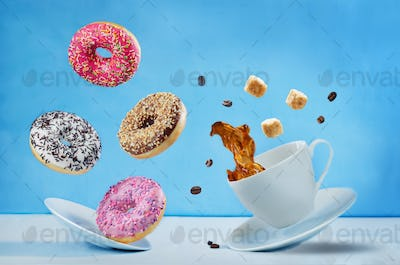 Flying cup of coffee with multicolored donuts