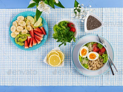 Breakfast bowl with oatmeal, tomatoes, lettuce, microgreens and boiled egg.