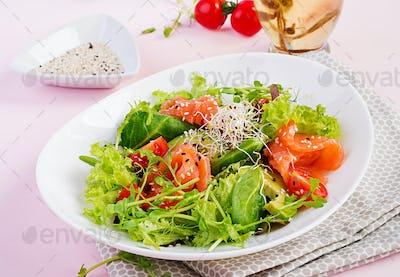 Healthy salad of fresh vegetables - tomatoes, avocado, arugula, seeds and salmon