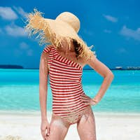 Woman in one-piece swimsuit at beach