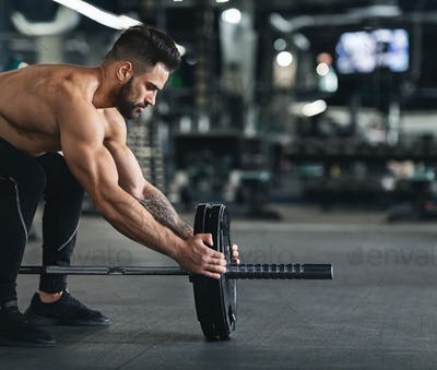 Muscular man changing weights of barbell, empty space