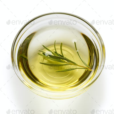 Glass bowl with olive oil on white