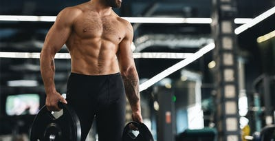 Muscular athlete with naked torso holding barbell plates