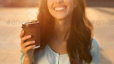 Happy woman enjoying takeaway coffee, walking outdoors