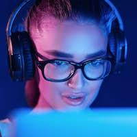 Female pro gamer playing video game, wearing headset