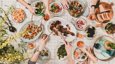 Flat-lay of hands of people eating and drinking rose wine