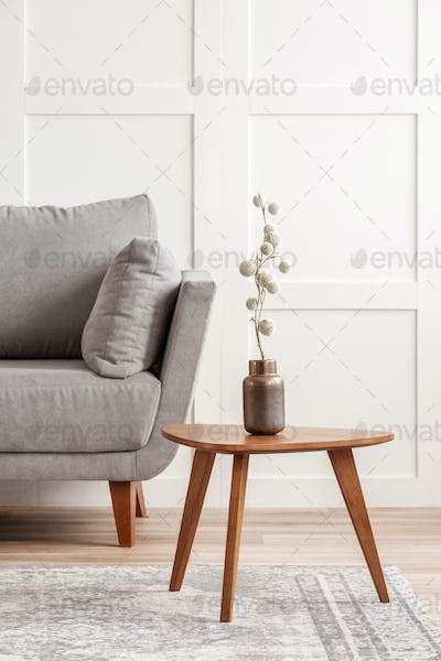 Cotton flower on stylish copper vase on small wooden coffee table next to grey settee