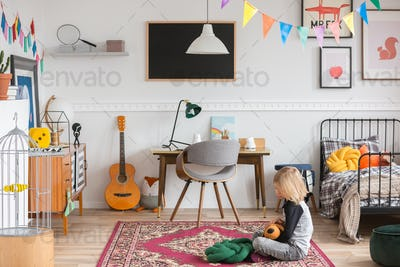 Little kid sitting on the rug in the white bedroom with vintage