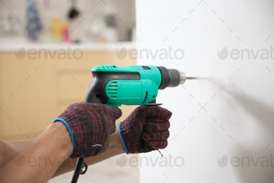 hands with gloves using electric drill