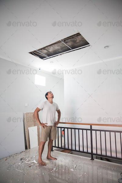 man looking up the broken ceiling