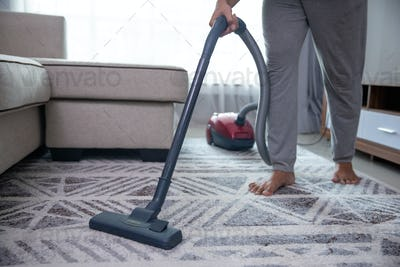 man hand vacuuming carpet