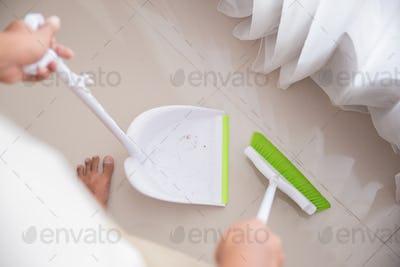 housekeeper is sweeping the floor