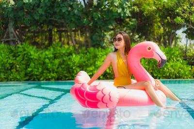 Portrait beautiful young asian woman on the flamingo inflatable