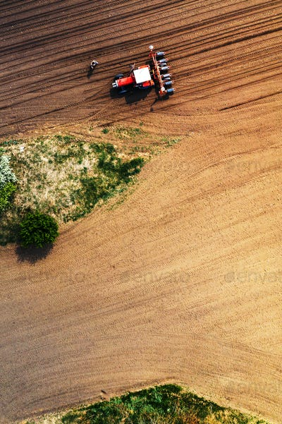 Farmer and tractor with seeder from drone pov